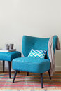 Retro teal armchair and matching ottoman with decor objects candles scarf book Royalty Free Stock Photography
