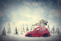 Retro toy car carrying tiny Christmas tree. Fairytale scenery with snow and forest. Royalty Free Stock Photo