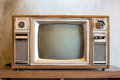 Retro tv with wooden case in room with vintage wallpaper Royalty Free Stock Photo