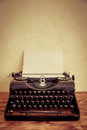 Retro typewriter with paper blank on wood table top view Royalty Free Stock Photo