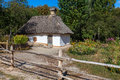 Retro ukrainian cottage with thatched roof and garden Royalty Free Stock Photo