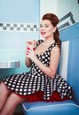 Retro vintage portrait of cheerful beautiful young girl sitting in cafe and drinking beverage. Pin up style portrait of young gi Royalty Free Stock Photo