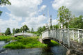 Retro white decorative bridges park stream river through water and cloudy blue sky Stock Image