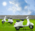 Retro white motorbike in the garden Royalty Free Stock Images