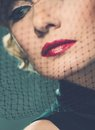 Retro woman elegant blond with red lipstick wearing little hat with veil Royalty Free Stock Photography