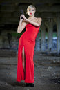 Retro woman with gun in red dress holding a old fabric ruins Royalty Free Stock Photos