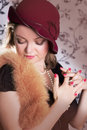 Retro woman in hat and boa with eyes closed over vintage back Stock Photos