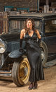 Retro woman near old car vintage automobile and beautiful in black dress Stock Image