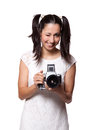 Retro woman with an old camera in white dress holding a and winks isolated on white background Stock Images