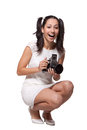 Retro woman with an old camera in white dress is squatting holding the and laughs isolated on white background Stock Photos