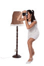 Retro woman with an old camera in white dress standing next to the lamp and take pictures isolated on white background Stock Photo