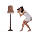 Retro woman with an old camera in white dress standing next to the lamp and take pictures isolated on white background Stock Image