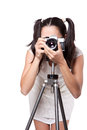 Retro woman with an old camera in white dress take pictures on a tripod isolated on white background Stock Photography