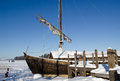 Retro wooden ship frozen lake ice sail people walk in near pier and on background of blue sky recreate in nature Stock Images
