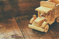 Retro wooden toy car over wooden table. room for text. nostalgia and simplicity concept. retro style image