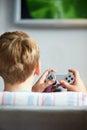 Retrovisione del regolatore playing video game della tenuta del ragazzo Fotografie Stock