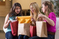 Return from shopping happy three girls browsing bags after Stock Photography