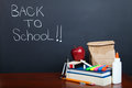 Return to school students supplies and lunch on desk in front of a chalkboard Royalty Free Stock Photography
