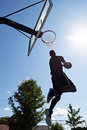 Reverse dunk back lit silhouette of a basketball player going up for a jam Stock Images