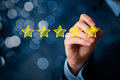 Review increase rating or ranking evaluation and classification concept businessman draw five yellow star to of Stock Photography