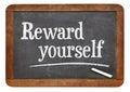 Reward yourself motivational words on a vintage slate blackboard Stock Image