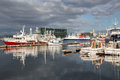 Reykjavik harbor with cargo ships ferryboats naval ships and small fishing boats the harpa and beautiful evening sky iceland Stock Image