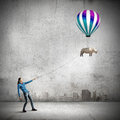 Rhino on lead young woman in casual and flying in sky Royalty Free Stock Photo