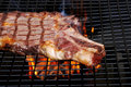 Rib steak on the barbecue wirh smoke and flames Stock Photography