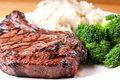 Rib steak with garlic mashed potatooes and brocolli juicy bbq potatoes Royalty Free Stock Images