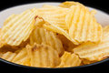 Ribbed potato chips in a bowl yellow black with white inside Royalty Free Stock Image