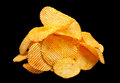 Ribbed potatoes chips on black snack with pepper isolated background Royalty Free Stock Photos