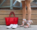 Ribbon Tie Stilleto shoe, sneakers and fashionable big red handbag. Fashionable woman with long beautiful legs standing Royalty Free Stock Photo