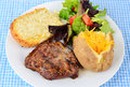 Ribeye steak and baked potato ribieye fresh off the grill with salad on white plate against blue gingham background with garlic Stock Photos