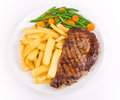 Ribeye steak with french fries and green beans from above over white background Royalty Free Stock Images