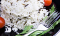 Rice with cherry tomatoes and greens on a black plate Royalty Free Stock Photo