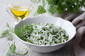 Rice with greens in a white bowl on a wooden table Royalty Free Stock Photo
