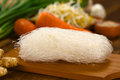 Rice noodles raw on wooden board with ginger and other vegetables selective focus focus on the front of the Stock Photos