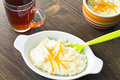 Rice pudding dessert topped with orange peel on a white plate Stock Images