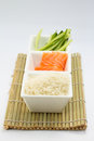 Rice salmon and sliced cucumber in white dish on bamboo mat Royalty Free Stock Photo