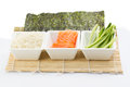 Rice salmon and sliced cucumber in white dish with nori on bamboo mat Royalty Free Stock Photo
