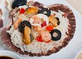 Rice in the shell, decorated with seafood, shrimps, mussels, squid rings and olives. Royalty Free Stock Photo