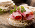 Rice wafers with salami topped and fresh herbs Stock Photo