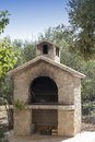 Rich bbq fireplace traditional made from brics in olive tree and fig tree mediterranean garden Royalty Free Stock Image