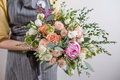 Rich bunch of pink peonies and white eustoma roses flowers, green leaf in glass vase. Fresh spring bouquet. Summer