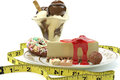 Rich calorie desserts surrounded by a measuring tape Royalty Free Stock Images