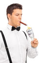 Rich man lighting up a cigar with burning dollar vertical shot of isolated on white background Royalty Free Stock Photo