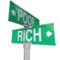 Rich vs poor two way street road signs poverty wealth words on a green or pointing to versus to illustrate the difference between Stock Images