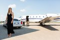 Rich woman in elegant dress at airport terminal full length of women standing against limousine and private Royalty Free Stock Image
