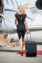 Rich woman with luggage walking towards private full length rear view of jet at airport terminal Stock Images