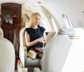 Rich woman using tablet computer im privatjet Lizenzfreie Stockfotos